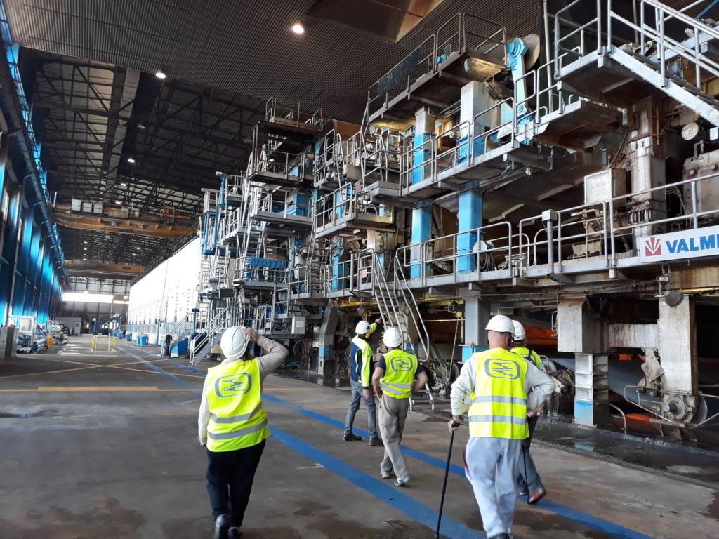 Intérieur de l'usine en arrière plan et une partie du groupe en marche