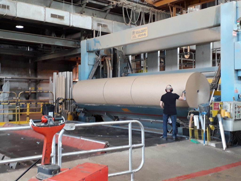Vue d'ensemble d'une partie de l'usine dont un homme près d'un énorme rouleau de papier kraft