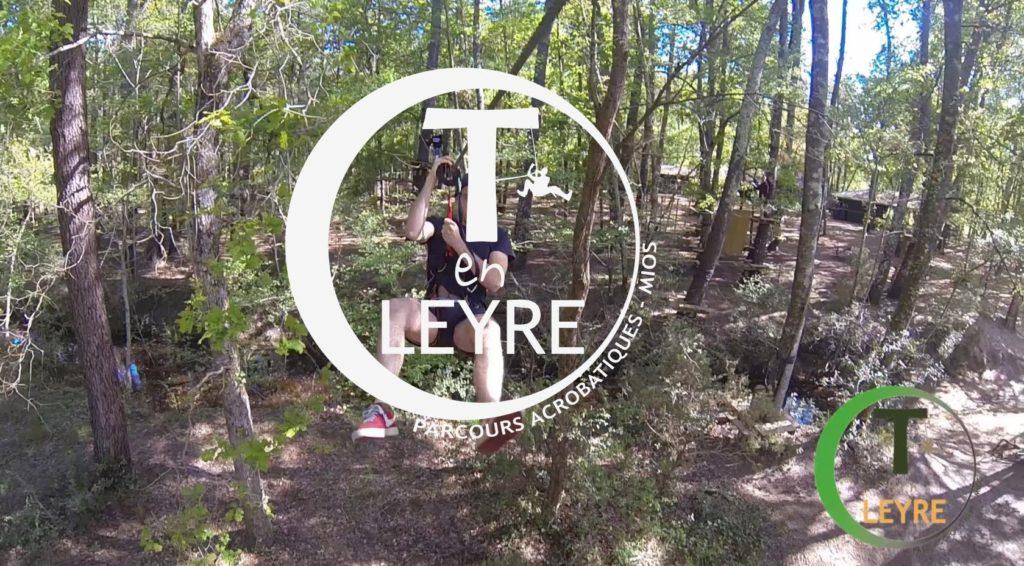 Logo T en Leyre, avec un fond d'arbres et des personnes en tirolienne
